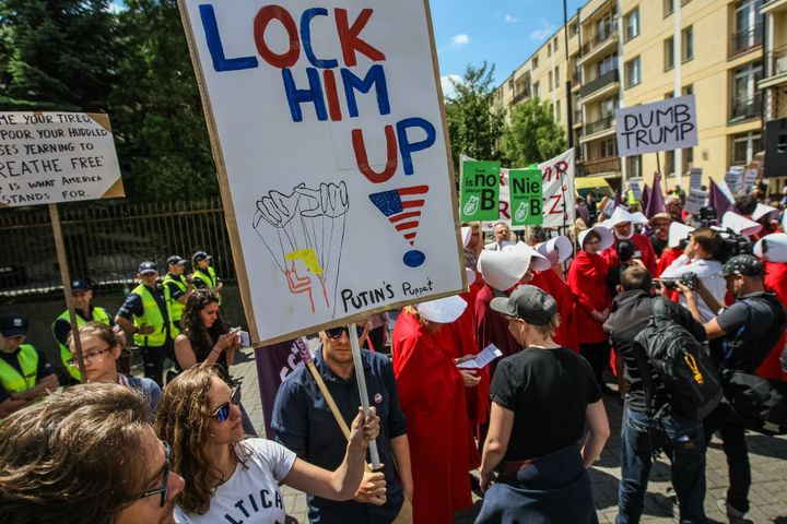 "A woman holds a sign that says ""Lock him up!"" next to protesters dressed as handmaids."
