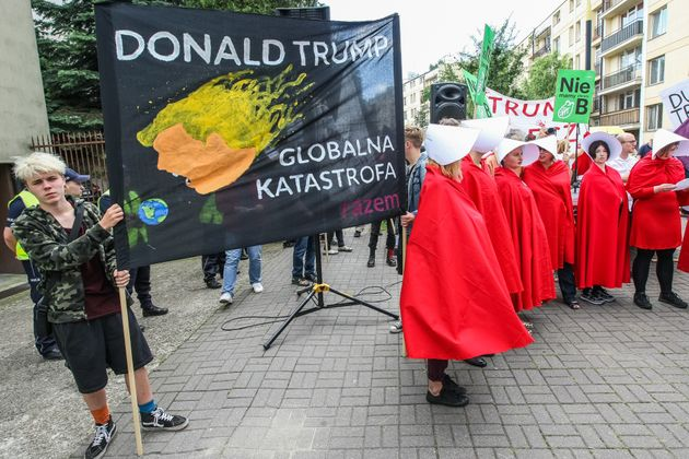 Woman dressed as as characters from The Handmaid's Tale and people holding anti-Trump posters and banners...
