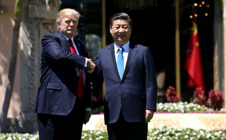 U.S. President Donald Trump and Chinese President Xi Jinping shake hands while walking at Mar-a-Lago estate after a bilateral