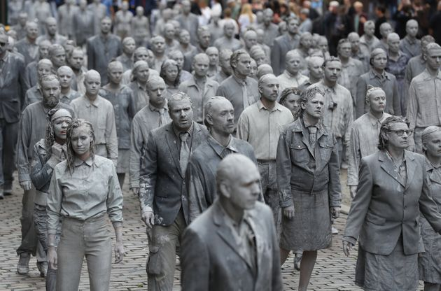 Performance artists covered in clay to look like zombies walk trance-like through the city center on...