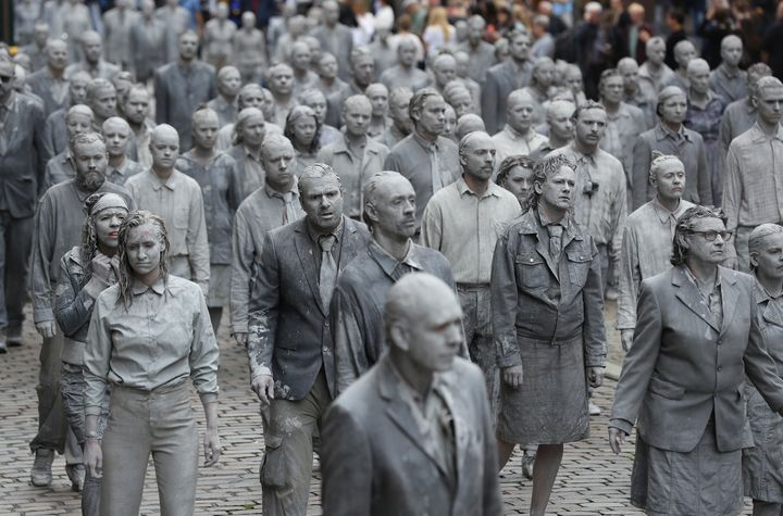 Performance artists covered in clay to look like zombies walk trance-like through the city center on July 5, 2017 in Hamburg,