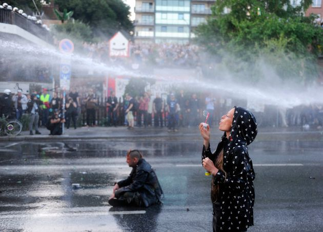 A protester blows bubbles as riot police use water cannons during the