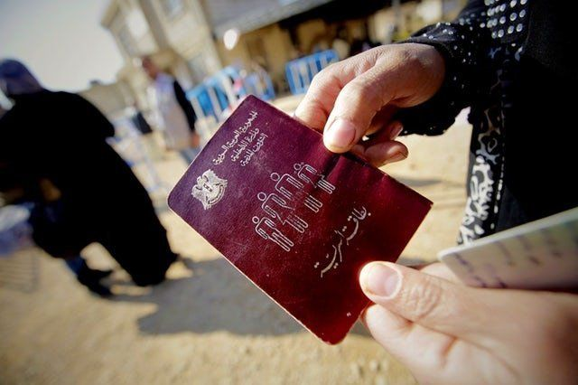 A Syrian woman shows her passport as families, who fled recent violence in the mountainous Qalamoun region, wait to be regist