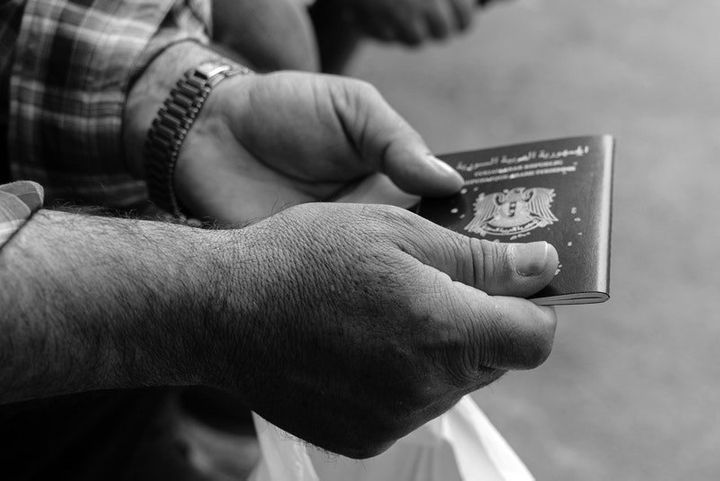A Syrian man holds his passport outside the Syrian consulate in Istanbul on May 4, 2017.