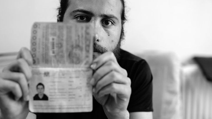 Zaher Said holds up his Syrian passport, which is about to expire, in his home in Gaziantep, Turkey on May 20, 2017.