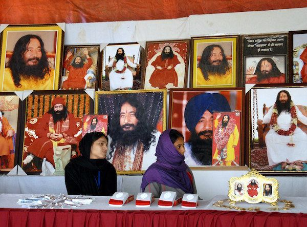 Indian followers of deceased guru Ashutosh Maharaj sit front posters bearing his image at a stall during...