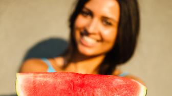 Smiling young woman giving watermelon slice to camera.