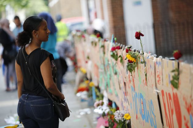 People pause in front of memorial tributes to the victims and the missing from the Grenfell Tower block...