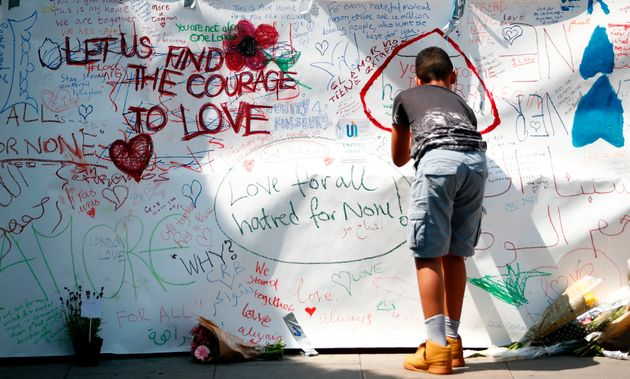 A boy writes a tributes near the scene of the 19 June van attack on pedestrians, in the Finsbury Park...