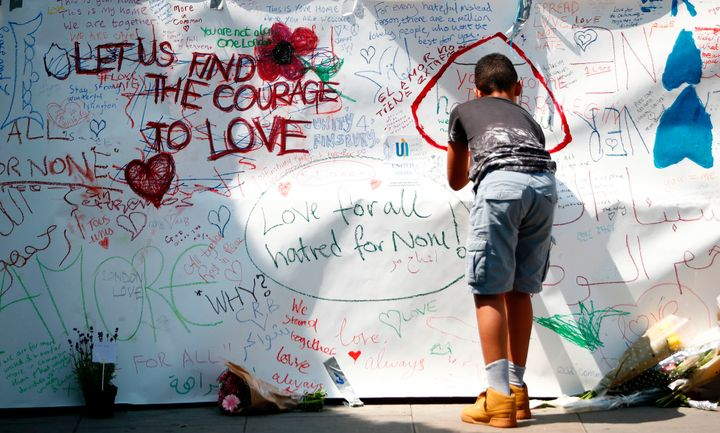 A boy writes a tributes near the scene of the 19 June van attack on pedestrians, in the Finsbury Park area of north London.