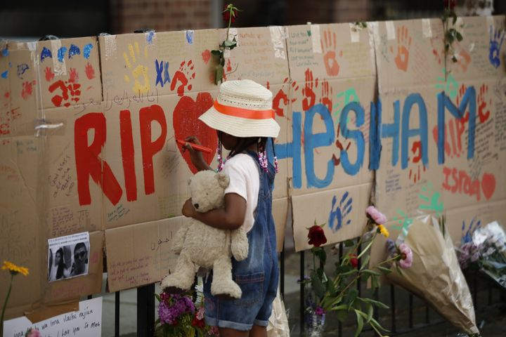 A girl draws on a memorial set against railings in tribute to the victims and the missing from the Grenfell Tower block fire close to the scene in North Kensington, west London.