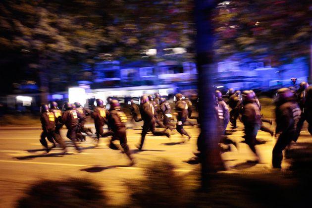 German anti-riot police rush towards protesters in