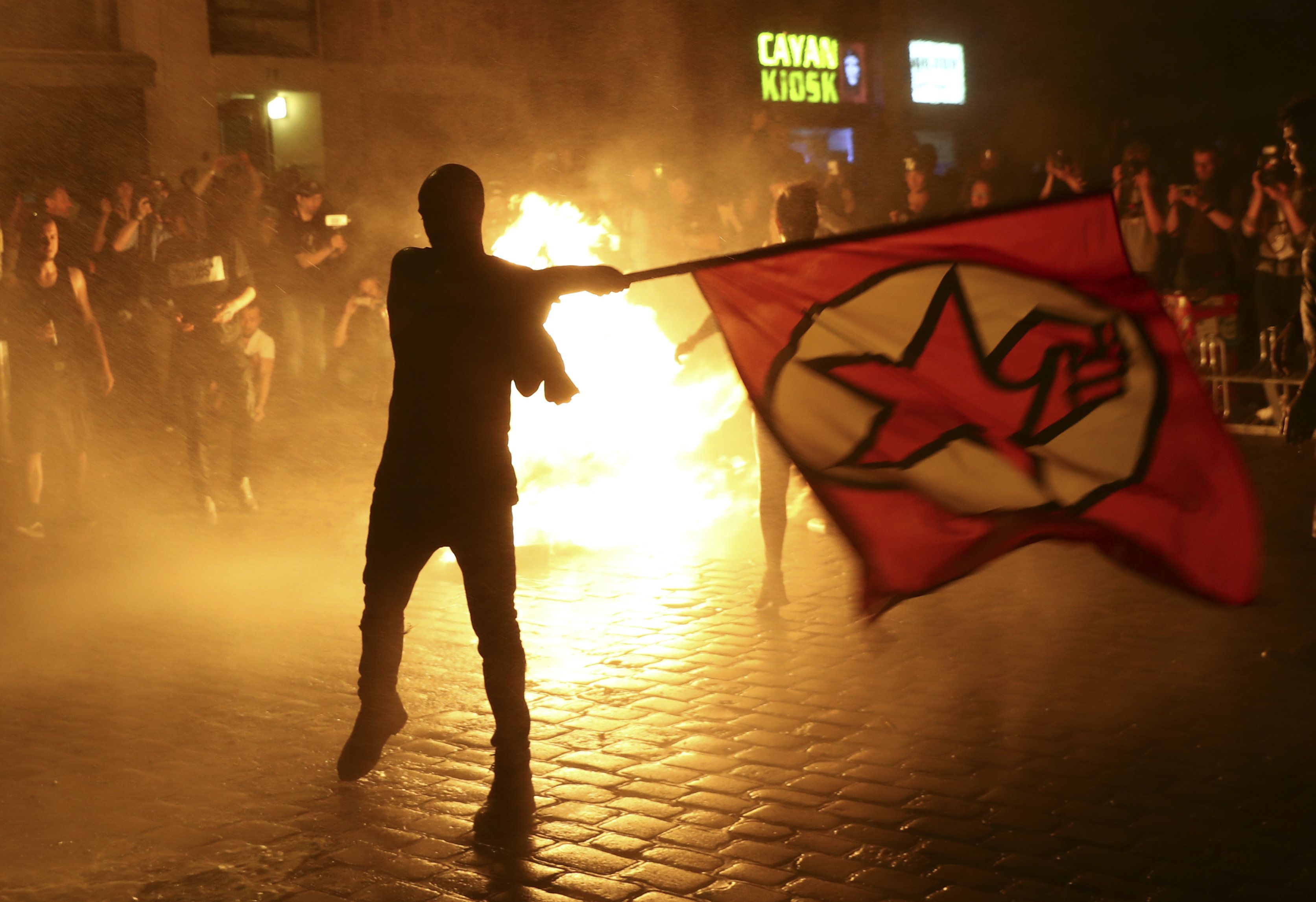 An anti-G20 protestor waves a flag in front of a burning