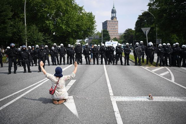 A demonstrator sits on the road in front of
