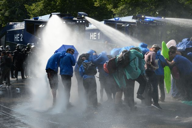 Demonstrators are hit by water cannons during protests on