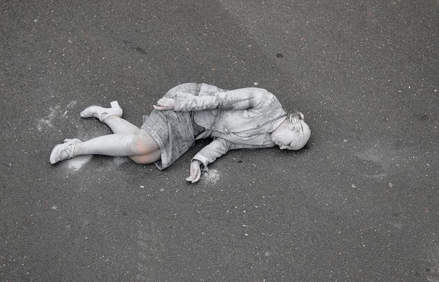 A woman painted grey lies on the ground as part of the