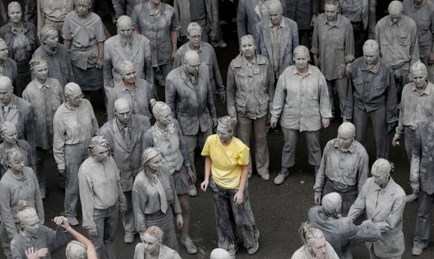 Performers began shedding their grey clothes to show bright clothing