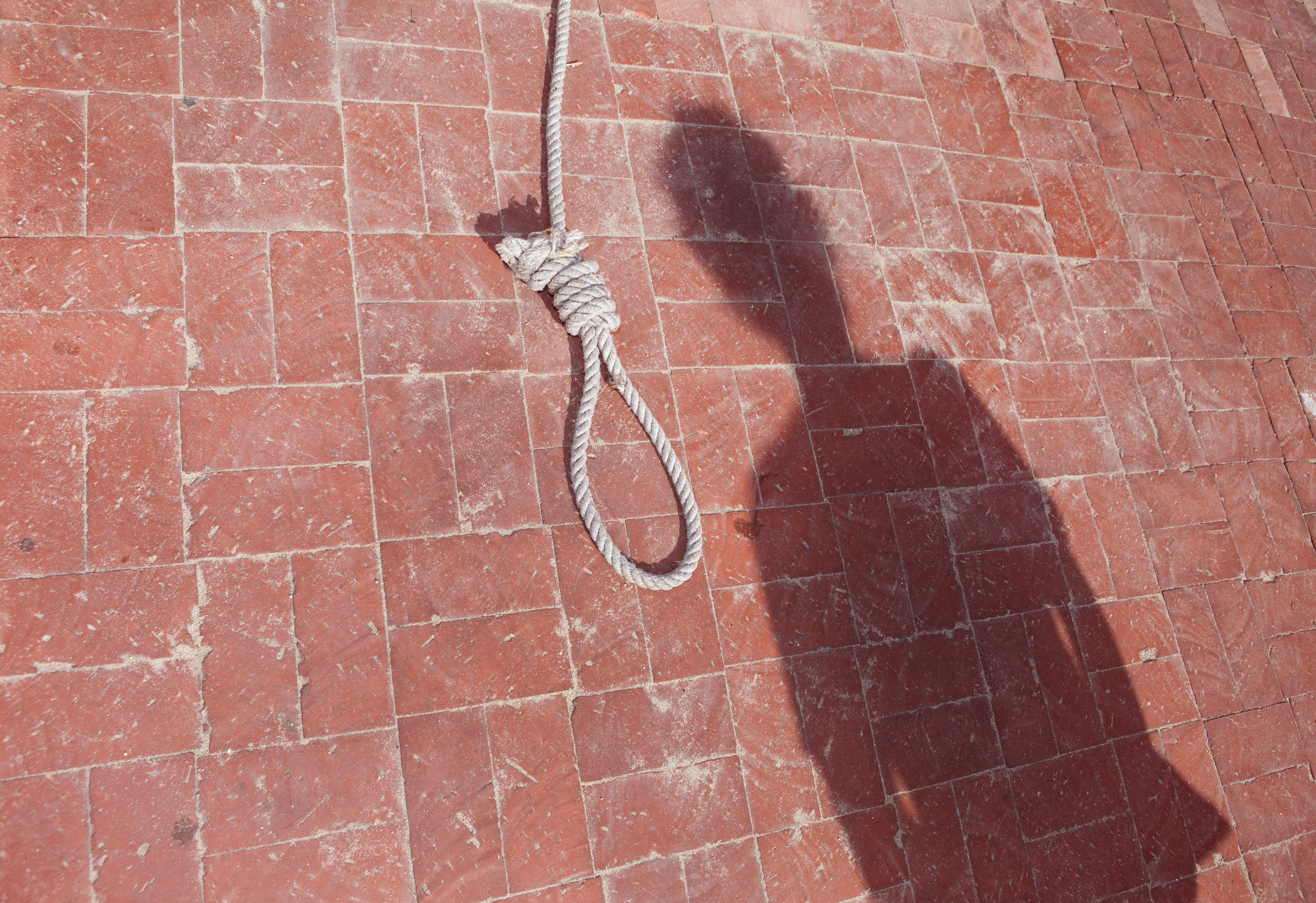 The shadow of a prisoner waits by the noose for a death penalty hanging.
