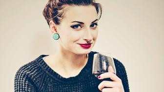 Young woman posing in her house drinking wine