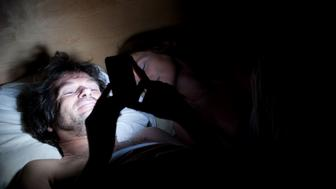 BXCHPR The affair. Man and woman in bed. Man is laughing at his iPhone, implying contact with another woman. His wife is asleep.