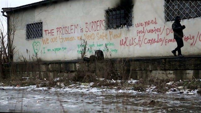 An asylum seeker walks past political graffiti at an abandoned warehouse close to Belgrade's main train station.