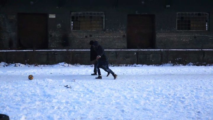 Young Afghan men play football in the snow outside the warehouses. Temperatures in Belgrade dipped to 1.5F (-17C) at night ov