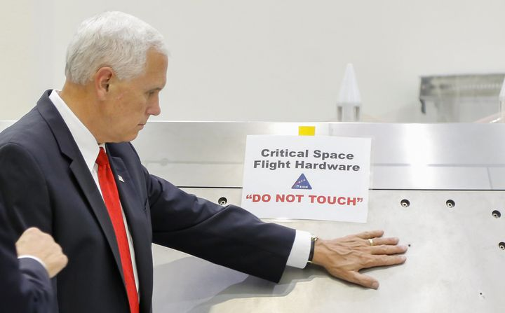 "U.S. Vice President Mike Pence touches a piece of hardware with a warning label ""Do Not Touch"" during a tour of the Operation"