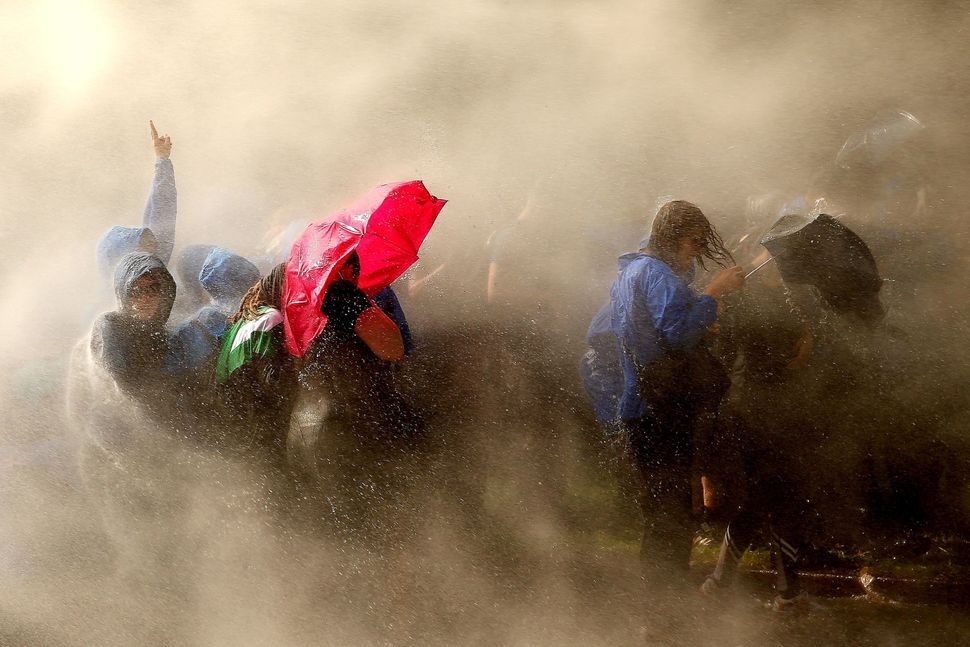 Demonstrators are hit by water cannons.
