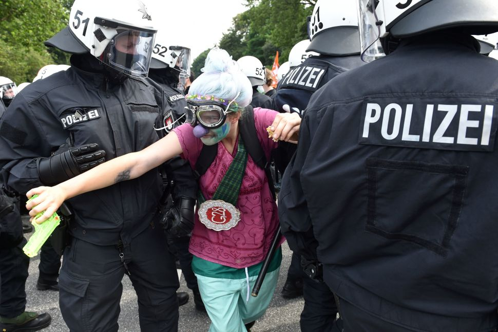Policemen lead away a demonstrator dressed as a clown.