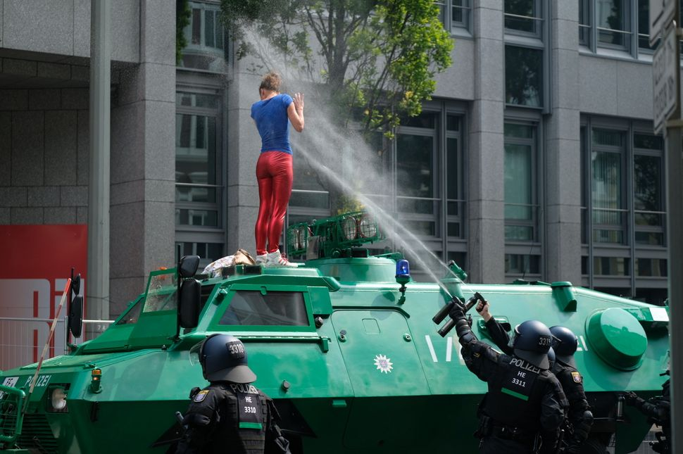 Policemen shoot pepper spray on a demonstrator who has climbed onto an armored vehicle.