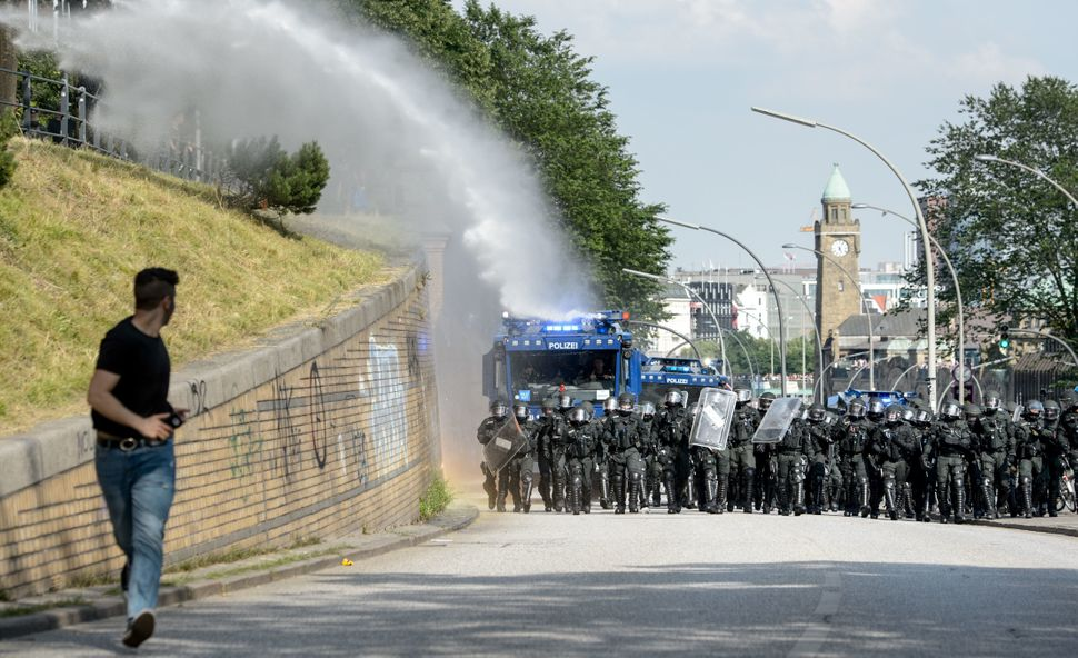 An anti-G-20 Summit demonstrator runs away from a police water cannon.