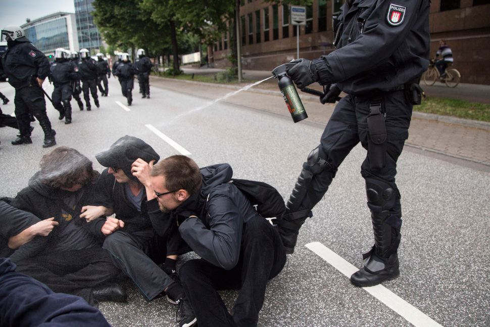 Policeman use pepper spray on protesters.