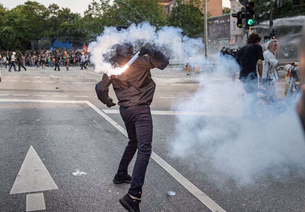 A demonstrator throws a firework against police units during an demonstration against the G-20 Summit on July 7, 2017 in Hamb
