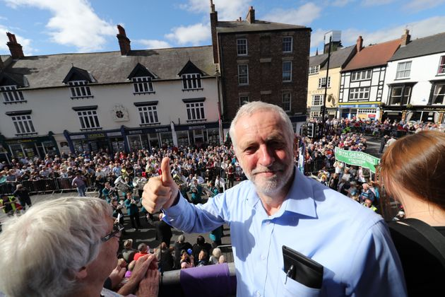 Labour leader Jeremy Corbyn watches the parade from the balcony of the Royal County Hotel during the...
