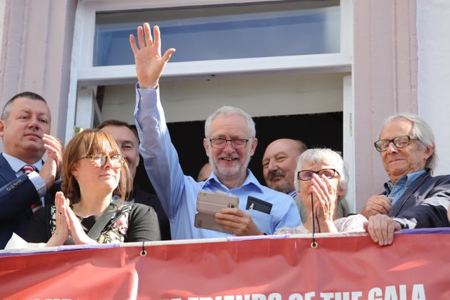 Labour leader Jeremy Corbyn (centre) and film director Ken Loach (right) watch the parade during the...