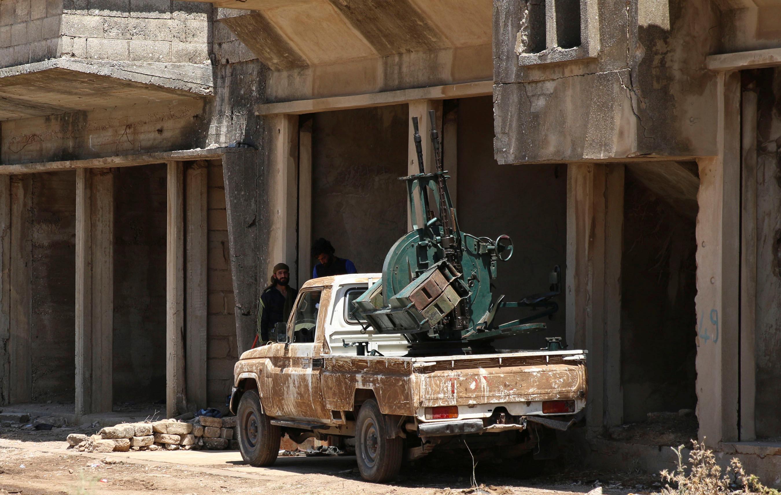 Free Syrian Army fighter stand near an anti-air craft machine gun in Quneitra, Syria July 8, 2017. REUTERS/Alaa al-Faqir