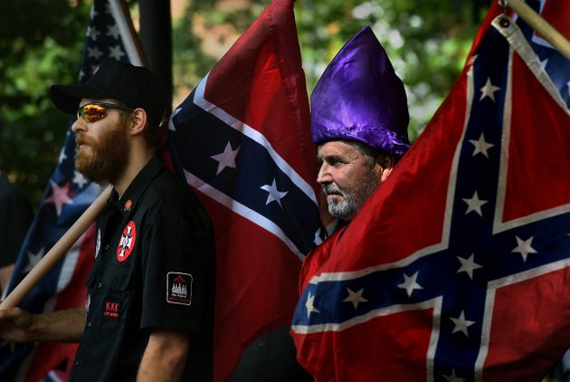 <strong>KKK members watch as anti-KKK groups chanted against