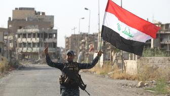 An Iraqi federal police member waves his country's national flag as he celebrates in the Old City of Mosul on July 9, 2017 after the government's announcement of the 'liberation' of the embattled city. Iraqi Prime Minister Haider al-Abadi's office said he was in 'liberated' Mosul to congratulate 'the heroic fighters and the Iraqi people on the achievement of the major victory'. / AFP PHOTO / AHMAD AL-RUBAYE        (Photo credit should read AHMAD AL-RUBAYE/AFP/Getty Images)
