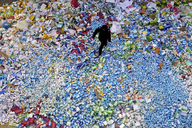 A Beijing policeman walks across a huge pile of fake medicines