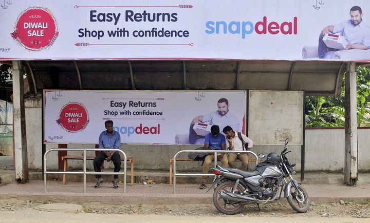 Commuters sit at a bus stop adorned with an advertisement of Indian online marketplace Snapdeal.