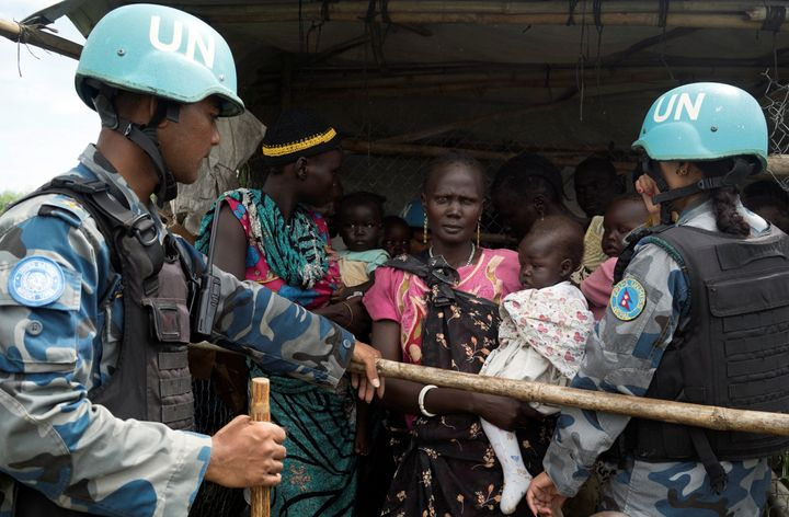 United Nations peacekeepers control South Sudanese women and children before the distribution of emergency food supplies in J