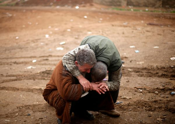 An Iraqi father (L) mourns the death of his son, who was killed during clashes in the Islamic State stronghold of Mosul on De