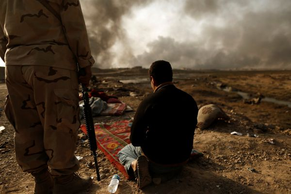 An Iraqi soldier stands next to a detained man accused of being an Islamic State fighter at a check point in Qayyara, south o