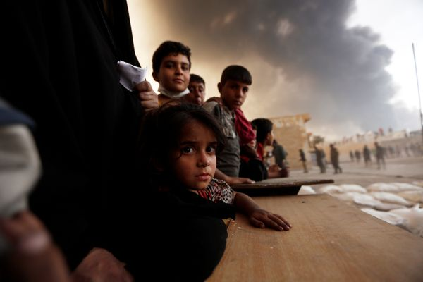 Newly displaced people wait to receive food supplies at a processing center for displaced people In Qayyara, south of Mosul,
