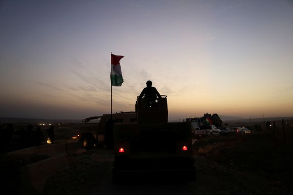 A Kurdish Peshmerga fighter looks over as he stands on the top of a humvee in front of an Islamic State militants' position o