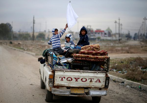 A displaced Iraqi boy holds a white flag as his family flees during the battle between Iraqi rapid response forces and Islami
