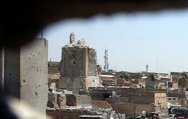 A destroyed al-Hadba minaret at Grand al-Nuri Mosque, left, is pictured through a hole at the Iraqi-held position at the Old