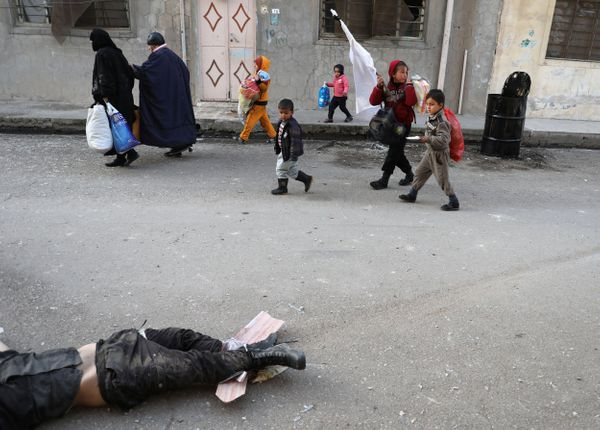 People who are trying to escape from Mosul walk in front of an Islamic State fighter on February 28, 2017.