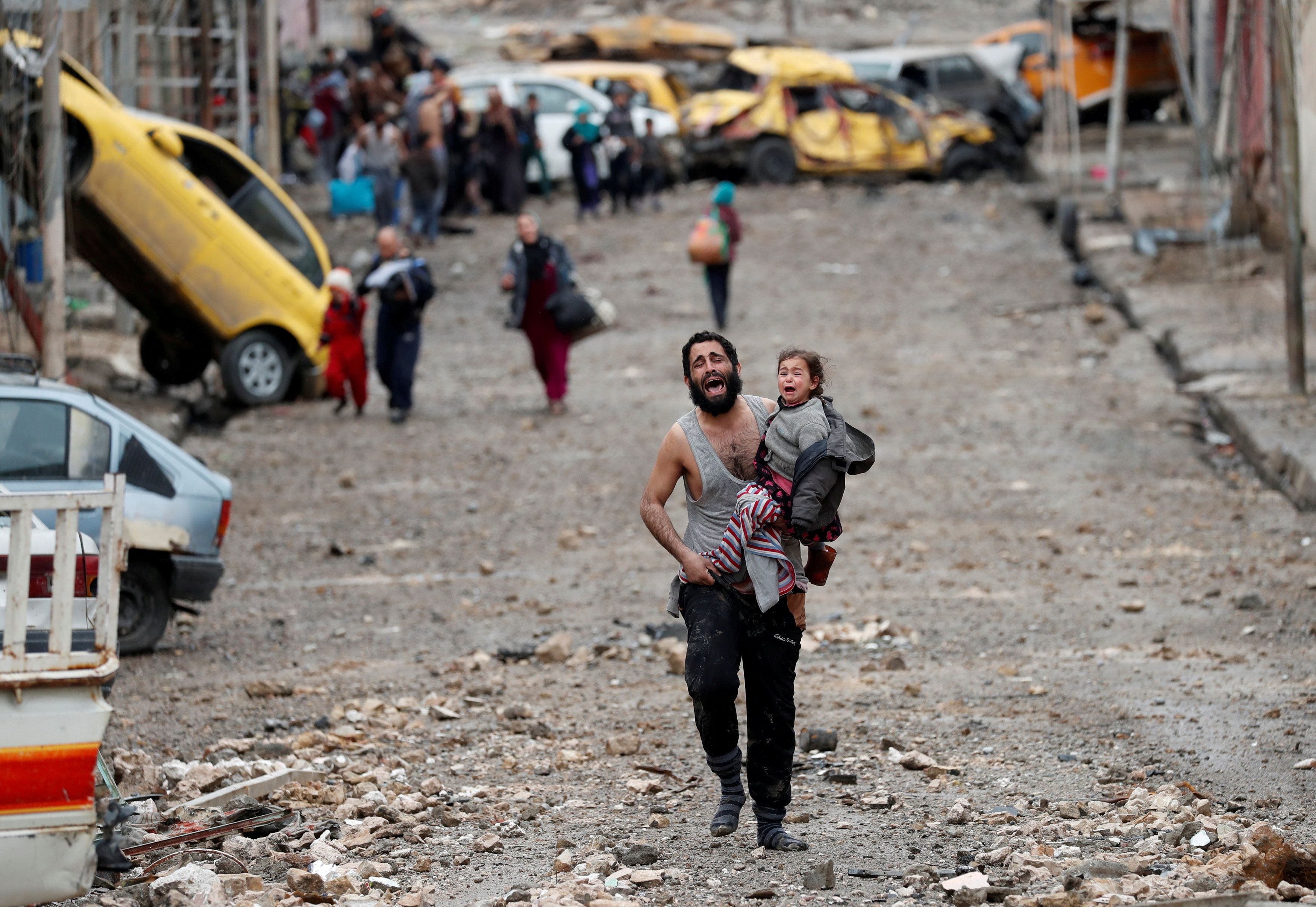 A man cries as he carries his daughter while walking from an Islamic State-controlled part of Mosul towards Iraqi special for