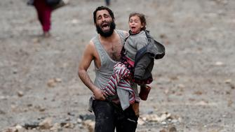 """A man cries as he carries his daughter while walking from an Islamic State-controlled part of Mosul towards Iraqi special forces soldiers during a battle in Mosul, Iraq March 4, 2017. Reuters Photographer Goran Tomasevic: """"Both screaming in terror, a father and the young daughter he cradled in his arm fled through the rubble-strewn streets of Wadi Hajar, transformed in a flash into a battleground between Islamic State fighters and Iraqi special forces. They and their neighbours - some wearing rubber sandals, some barefoot -  were running from an IS counter-attack in this part of Mosul, dodging gunfire as the militants closed in. When they reached the special forces lines, males were ordered to lift their shirts to prove they weren't suicide bombers. Some had to take off their clothes or show their belts, though not those carrying children. The father was so beside himself, so panicked. It was obvious because he had a short shirt on and was carrying a child that he wasn?t Islamic State. I believe they will both be taken to a refugee camp."""" REUTERS/Goran Tomasevic  SEARCH """"TOMASEVIC FATHER"""" FOR THIS STORY. SEARCH """"WIDER IMAGE"""" FOR ALL STORIES. TPX IMAGES OF THE DAY"""